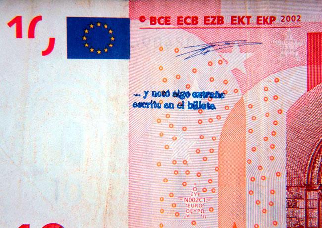 '...y notó algo extraño escrito en el billete' , 2002 Text translation: '... and noticed something strange written on the note'  Sellado de billetes durante un año / Stamping of bank notes for one year